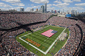 The national anthem is sung as a stealth bomber flies overhead during the pregame ceremonies of the game between the Chicago Bears and the Green Bay...