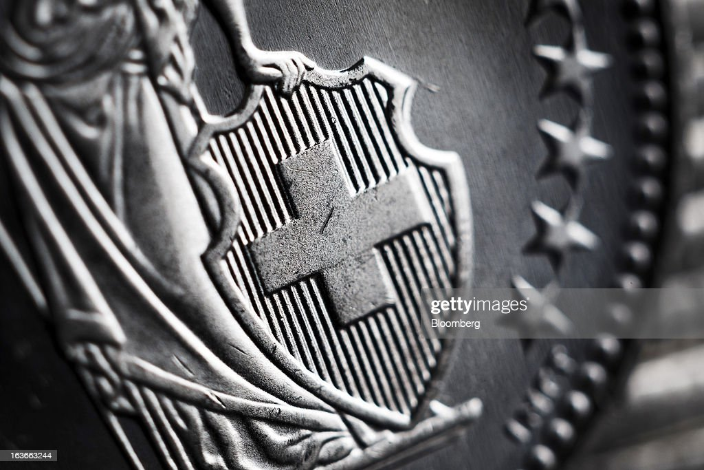 The national emblem of Switzerland sits in the center of a Swiss one franc coin in this arranged photograph in Lavigny, Switzerland, on Wednesday, March 13, 2013. The Swiss central bank pledged to keep up its defense of the franc cap after almost doubling its currency holdings to shield the country from the fallout caused by the euro zone's crisis. Photographer: Valentin Flauraud/Bloomberg via Getty Images