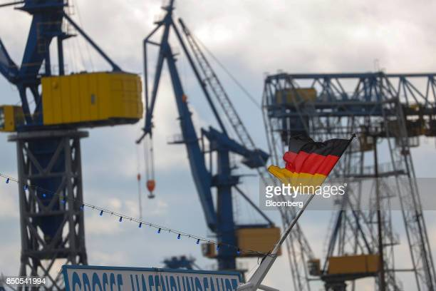 The national flag of Germany flies as shipping cranes stand at Blohm Voss maintenance shipyard at the Port of Hamburg in Hamburg Germany on Wednesday...