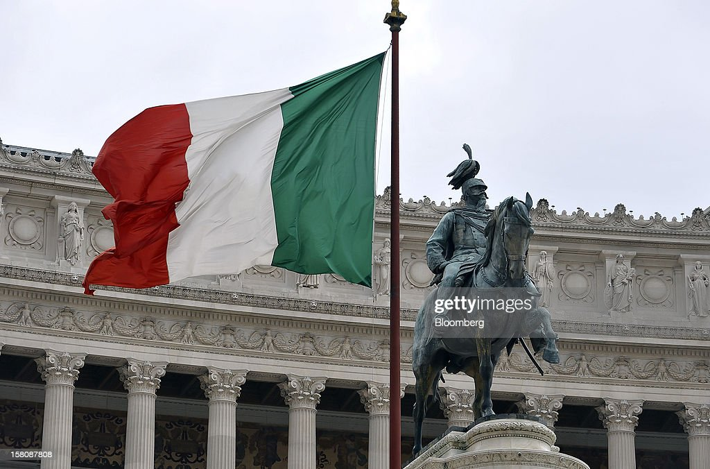 The national flag of Italy flies in front of a monument to the unknown soldier in Rome, Italy, on Monday, Dec. 10, 2012. The imminent end of Prime Minister Mario Monti's government fueled the largest increase in Italian borrowing costs in four months and threatened to open a new front in Europe's crisis fight before a year-end summit. Photographer: Victor Sokolowicz/Bloomberg via Getty Images