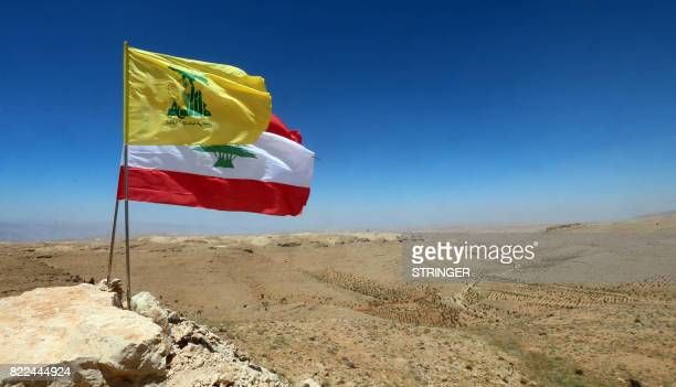 The national flag of Lebanon and the flag of Lebanese Shiite movement Hezbollah are seen placed amidst rocks during a press tour organised by...