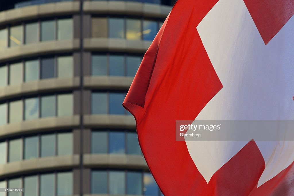 The national flag of Switzerland flies outside the headquarters of the Bank for International Settlements (BIS) in Basel, Switzerland, on Tuesday, June 25, 2013. Central banks can't expand loose monetary policy without exacerbating risks to world economies, the Bank for International Settlements said this week. Photographer: Gianluca Colla/Bloomberg via Getty Images