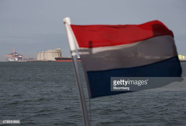 The national flag of the Netherlands flies from a sightseeing ferry as storage tanks and ship to shore cranes are seen beyond at the Gate liquid...