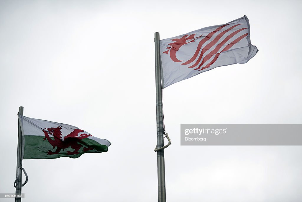 The national flag of Wales, left, and the logo of the Senedd, or National Assembly for Wales, fly from flagpoles in Cardiff, U.K. on Thursday, May 23, 2013. Bank of England Markets Director Paul Fisher said policy makers must continue to provide support to the British economy so that companies and consumers have room to reduce debts and rebuild confidence. Photographer: Simon Dawson/Bloomberg via Getty Images