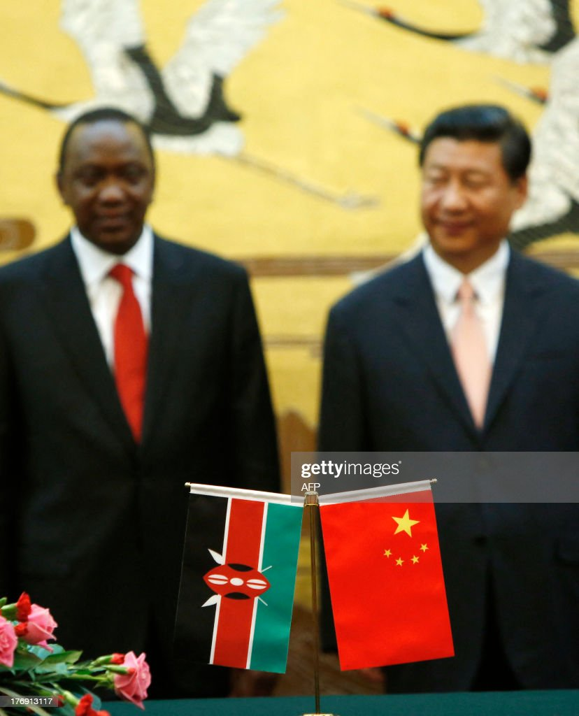 The national flags of Kenya and China are displayed on a table before Kenya's President Uhuru Kenyatta (L) and his Chinese counterpart Xi Jinping (R) during a ceremony at the Great Hall of the People in Beijing on August 19, 2013. Kenyatta, who faces trial on charges of crimes against humanity, was welcomed to China on August 19 with a 21-gun salute and a meeting with President Xi Jinping. AFP PHOTO / POOL / HOW HWEE YOUNG