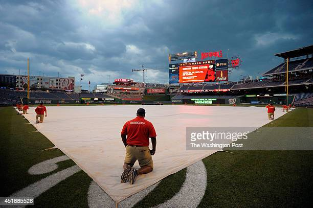 The Nationals ground crew holds down the tarp as server weather approaches the stadium delaying the start of the Baltimore Orioles vs the Washington...