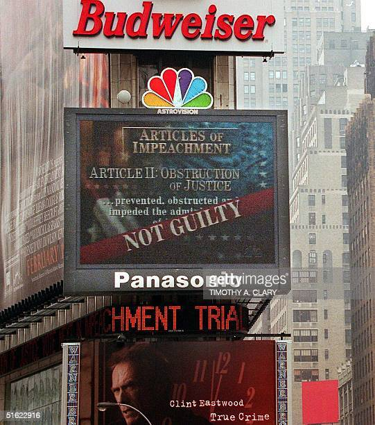 The NBC jumbotron at Times Square in New York displays the 'Not Guilty' verdict on the Obstruction of Justice charge against US President Bill...
