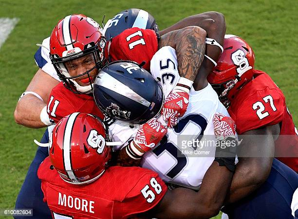 The NC State Wolfpack's Josh Jones leads a tackle of Jeremy Cox of the Old Dominion Monarchs with the help of Airius Moore and Justin Jones at...