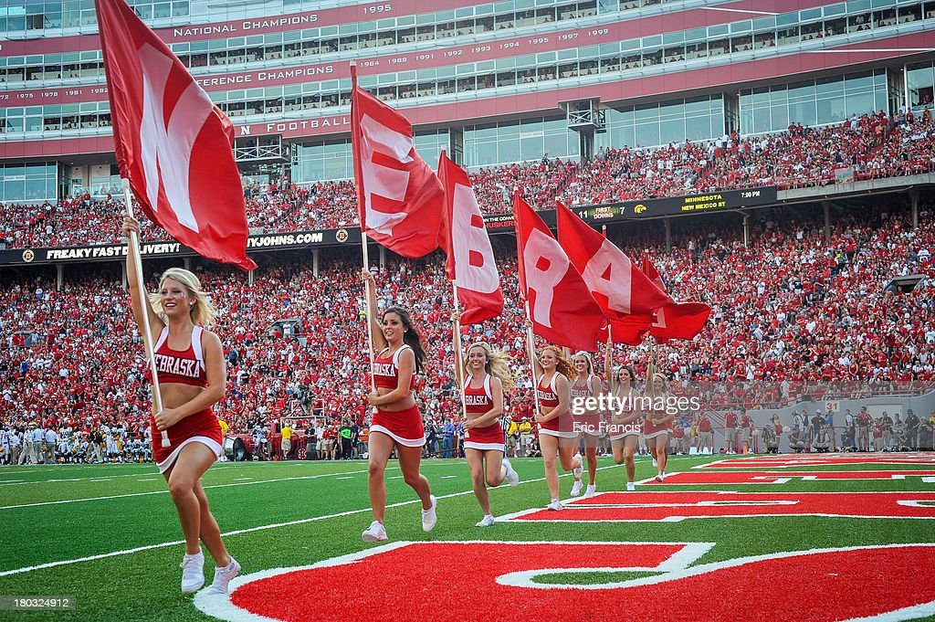 The Nebraska Cornhuskers cheer leaders race across the end zone with flags after a touch down during theigame against the Southern Miss Golden Eagles at Memorial Stadium on September 7, 2013 in Lincoln, Nebraska.
