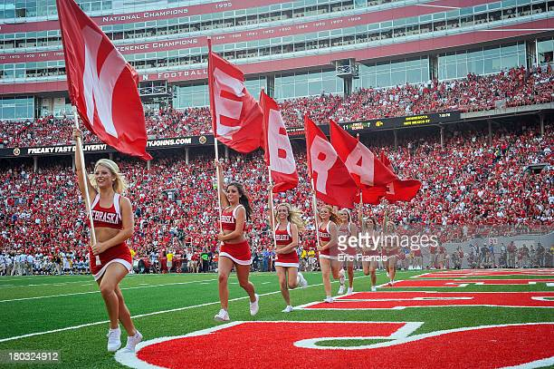 The Nebraska Cornhuskers cheer leaders race across the end zone with flags after a touch down during theigame against the Southern Miss Golden Eagles...