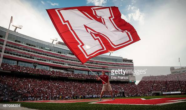 The Nebraska Cornhuskers cheer squad waves a giant flag after a touchdown during their game against the Brigham Young Cougars at Memorial Stadium on...