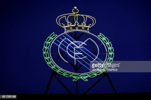 The neon Real Madrid badge glows against the night sky