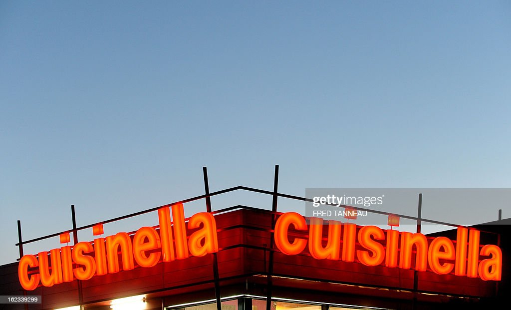 The neon sign of a Cuisinella kitchen and accessories' store is pictured February 21, 2013 in Douarnenez, western of France. AFP PHOTO FRED TANNEAU