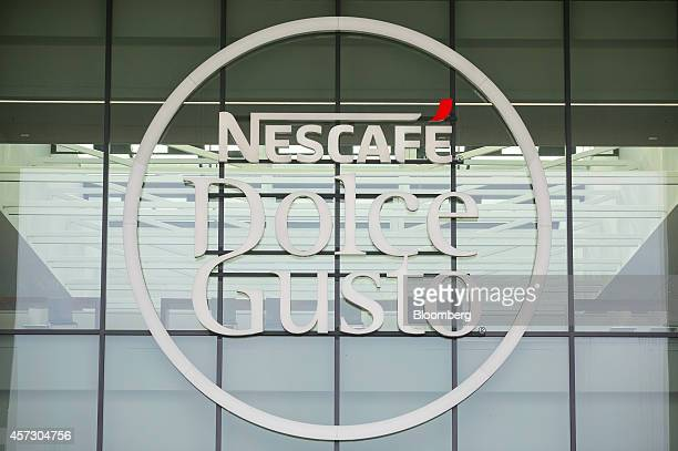 The Nescafe Dolce Gusto coffee logo sits on display on the windows of the Nestle SA factory in Schwerin Germany on Thursday Oct 16 2014 The factory...