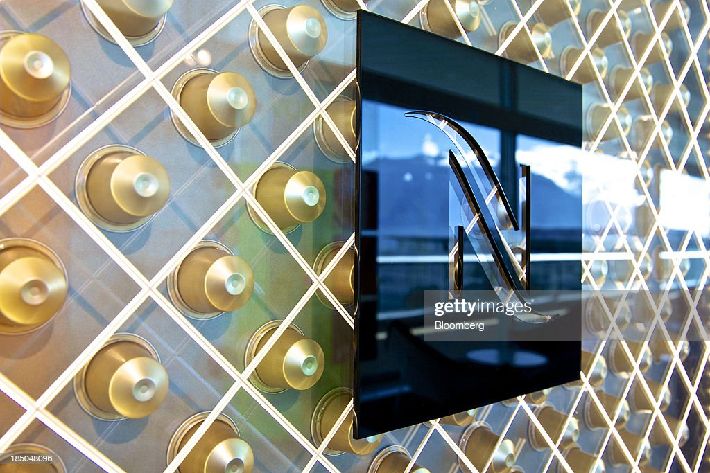 The Nespresso logo sits on a wall decorated with single-serve coffee capsules inside Nestle SA's headquarters in Vevey, Switzerland, on Thursday, Oct. 17, 2013. Nestle SA, the world's biggest food company, reported nine-month sales that were below its full-year target rate, highlighting the difficult environment faced by the makers of consumer products. Photographer: Gianluca Colla/Bloomberg via Getty Images