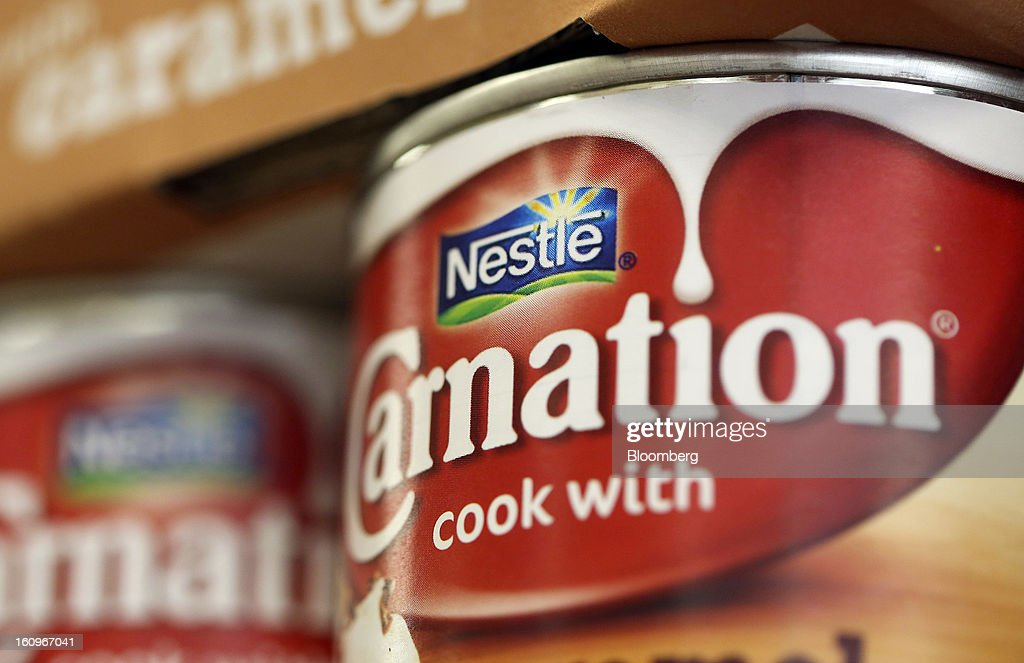 The Nestle SA logo sits on a tin of the company's Carnation brand evaporated milk, inside a supermarket in London, U.K., on Friday, Feb. 8, 2013. Britain's economy will grow more slowly this year than previously forecast and stagnation may persist, according to the National Institute of Economic and Social Research. Photographer: Chris Ratcliffe/Bloomberg via Getty Images