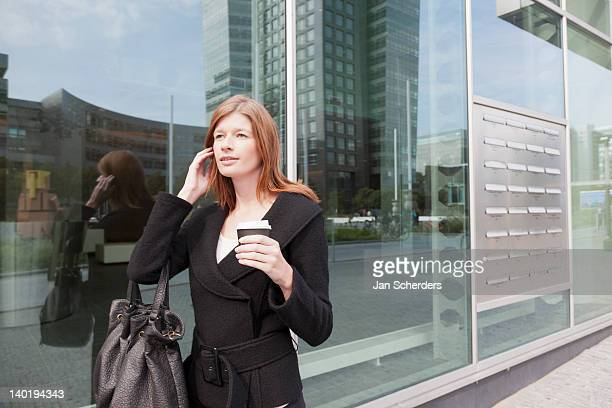 The Netherlands, Amsterdam, Businesswoman walking with coffee and phone