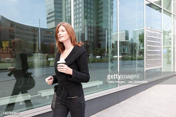 The Netherlands, Amsterdam, Businesswoman walking with coffee