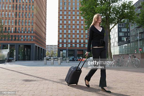 The Netherlands, Amsterdam, Businesswoman walking with luggage