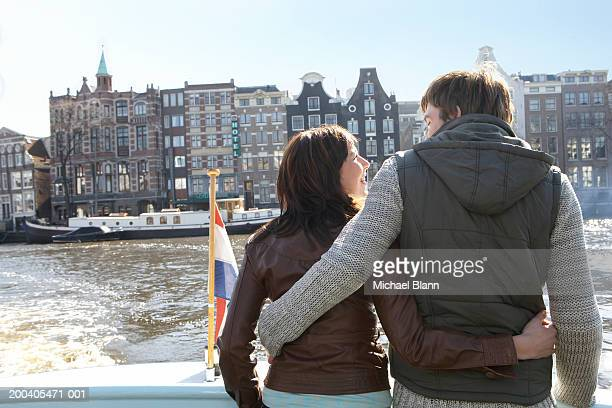 The Netherlands, Amsterdam, couple arm in arm on boat, rear view