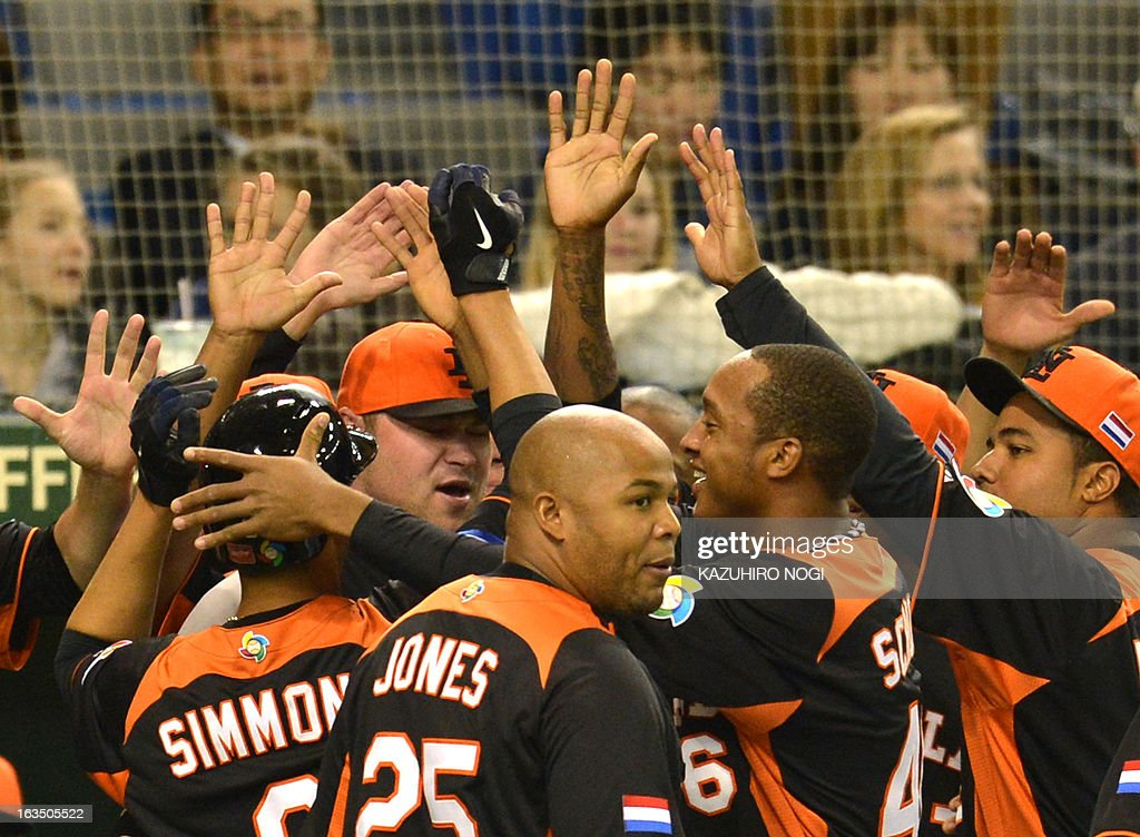 The Netherlands Andruw Jones (C, #25) and teammates celebrate after scoring against Cuba during the third inning of their second-round Pool 1 game in the World Baseball Classic tournament at Tokyo Dome on March 11, 2013. AFP PHOTO / KAZUHIRO NOGI