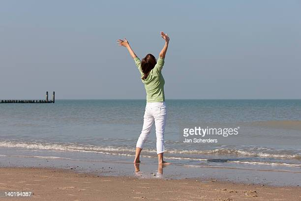 The Netherlands, Domburg, Woman on beach with arms raised