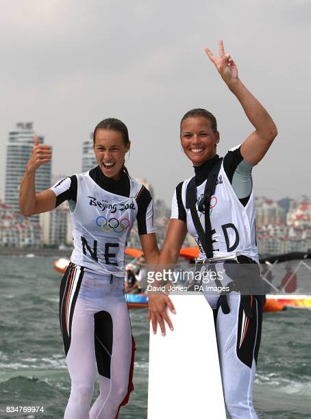 The Netherlands' Marcelien de Koning and Lobke Berkhout stand on the keel of their boat after capsizing at the end of the Women's 470 Women Medal...
