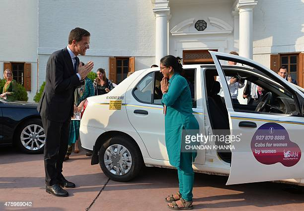 The Netherlands' Prime Minister Mark Rutte greets Indian cab driver Shanti Devi Sharma during an event to promote the 'Women on Wheels' cabs for...
