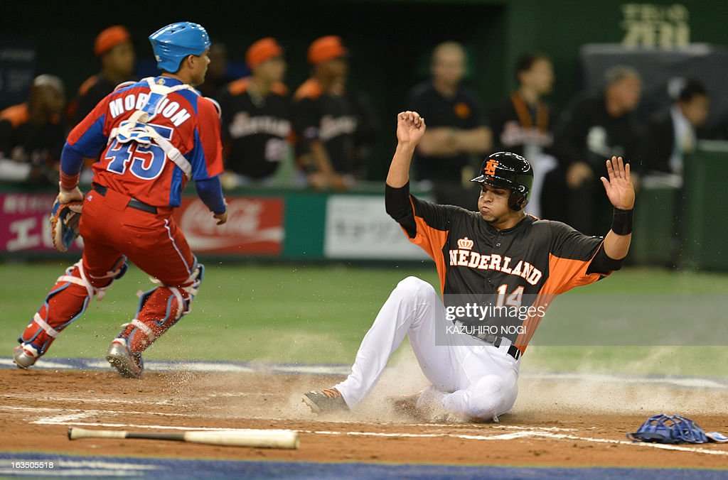 The Netherlands Randolph Oduber (R) slides into home-plate against Cuba during the third inning of their second-round Pool 1 game in the World Baseball Classic tournament at Tokyo Dome on March 11, 2013.