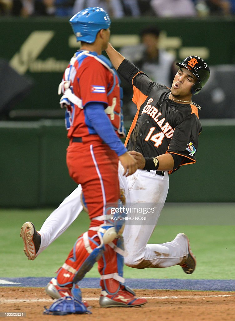 The Netherlands Randolph Oduber (R) slides into home-plate as Cuba's catcher Frank Morejon looks on during the fourth inning of their second-round Pool 1 game in the World Baseball Classic tournament at Tokyo Dome on March 11, 2013.