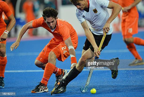 The Netherlands' Robert Van Der Horst vies with Germany's Florian Fuchs during the men's field hockey gold medal match Germany vs the Netherlands at...