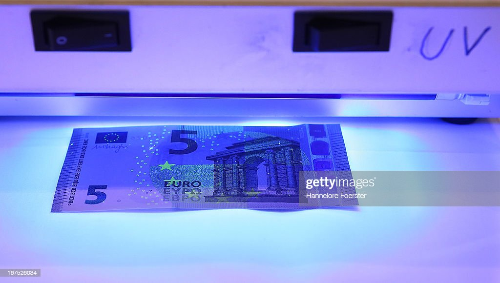 The new 5 Euro note is displayed under a UV light at the German Bundesbank Counterfeit Money Analysis Lab during a demonstration for the media on April 26, 2013 in Mainz, Germany. The center is Germany's main facility for analysing potentially counterfeit money and also repairs damaged banknotes.