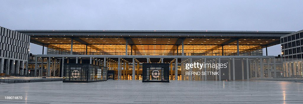 The new Berlin-Brandenburg Airport is lit up on January 7, 2013.The opening of Berlin's new main airport has been postponed indefinitely after several previous delays, the city's mayor said on January 7, 2013, in a fresh blow for the German capital and its top official. AFP PHOTO / BERND SETTNIK GERMANY OUT