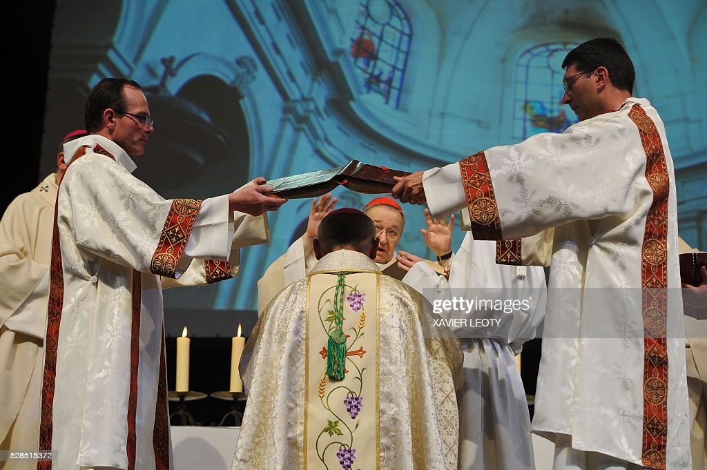 The new bishop of La Rochelle Georges Colomb (C) knees during his episcopal ordination by the Archbishop of Paris Mgr Andre Armand Vingt-Trois (C back) on May 5, 2016 at the Parc des expositions in La Rochelle, western France. / AFP / XAVIER
