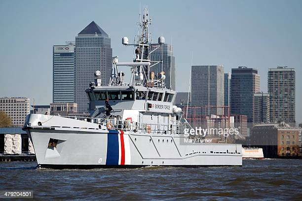The new Border Force cutter HMC Protector makes her way up the River Thames past the Canary Wharf skyline on March 16 2014 in London England The...