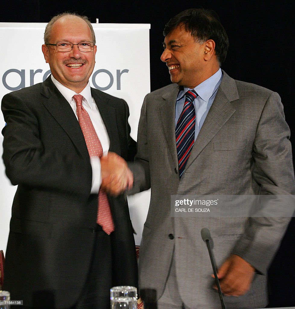 The new CEO of Steel Company Arcelor Mittal Roland Junck shakes hands with President of the company Lakshmi Mittal during a press conference in...