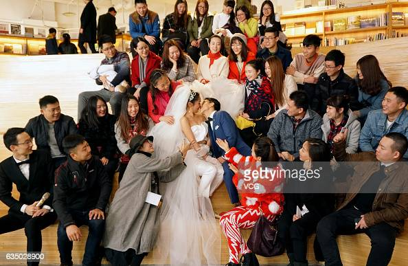 The new couple surrounded by wedding guests kisses at a bookstore where they hold a wedding ceremony on February 12 2017 in Chongqing China They...
