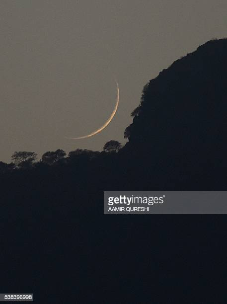 The new Crescent moon is seen above the Margala Hills to mark the begining of the of the Islamic holy month of Ramadan in Islamabad on June 6 2016...