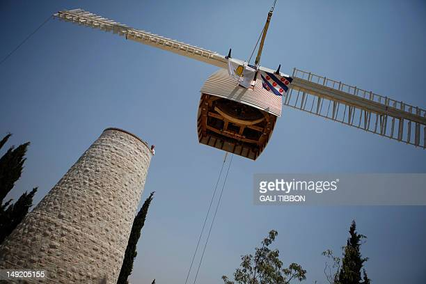 The new cupola and blades of the Sir Moses Montefiore's windmill are being lifted to the top of the windmill on July 25 2012 after a six months...