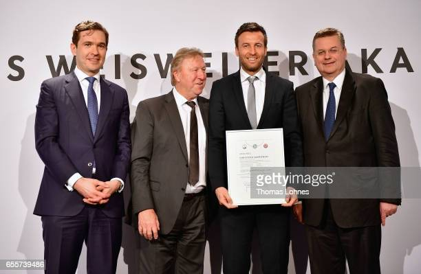 The new DFB football coach Christoph Dabrowski stands with his certificate between DFB general secretary Friedrich Curtius Horst Hrubesch and DFB...