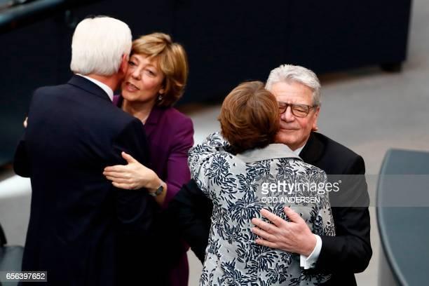 The new German President FrankWalter Steinmeier and his wife Elke Buedenbender hug Germany's outgoing President Joachim Gauck and his partner Daniela...
