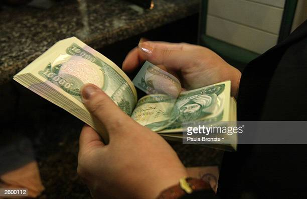 The new Iraqi dinar is being counted ready for distribution at the Bank of Baghdad October 152003 in Baghdad Iraq as the currency is introduced today...