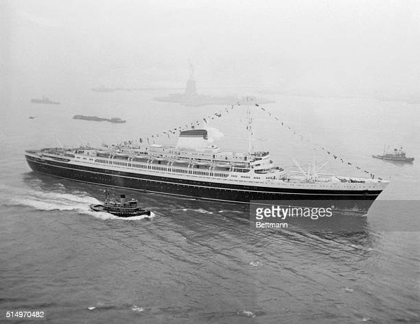 The new Italian liner Andrea Doria glides past the Statue of Liberty as she makes her way to her Manhattan Pier here upon completion of her maiden...