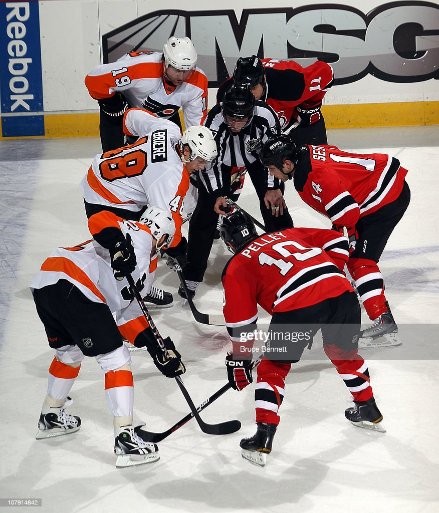 The New Jersey Devils and the Philadelphia Flyers take a second period faceoff at the Prudential Center on January 6, 2011 in Newark, New Jersey.