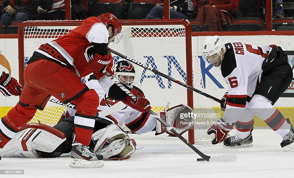 The New Jersey Devils' Martin Brodeur (30) and Andy Greene (6) defend the goal against the Carolina Hurricanes' Jiri Tlusty during the first period at the PNC Arena in Raleigh, North Carolina, on Thursday, March 21, 2013.