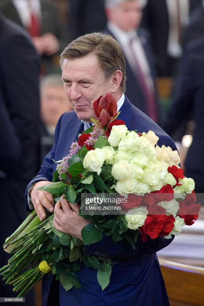 The new Latvian Prime Minister Maris Kucinskis holds flowers after his election at the Parliament of Latvia in Riga on February 11, 2016. / AFP / afp / Ilmars Znotins