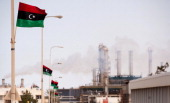 The new Libyan flag flutters outside an oil refinery in Zawiya on September 23 2011 Total SA's Libyan jointventure is set to restart oil production...