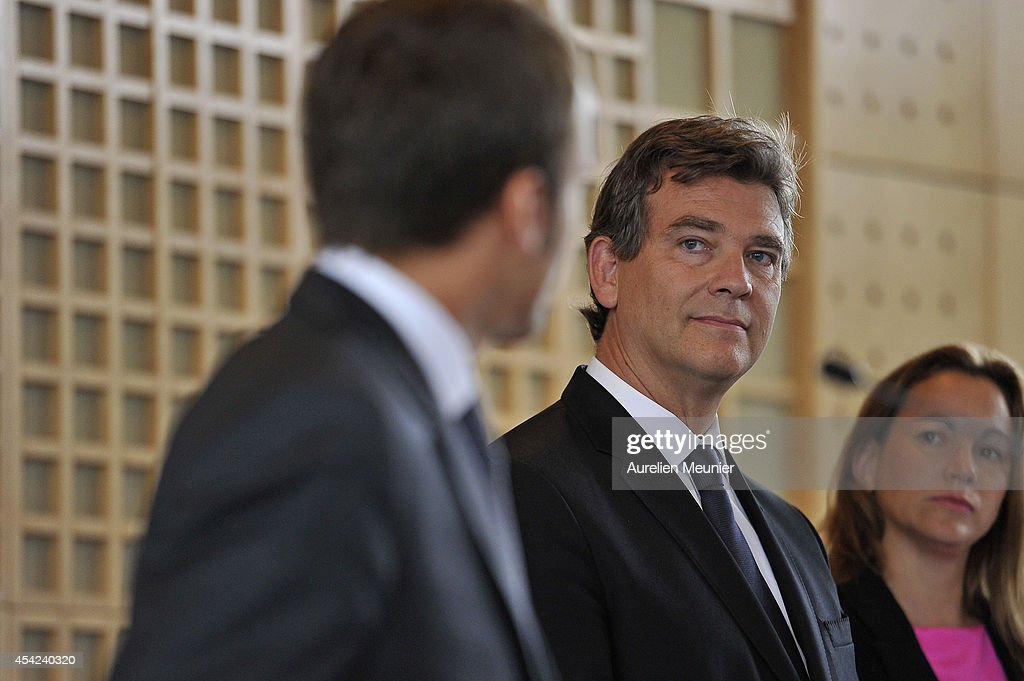 The new Minister of Finance, <a gi-track='captionPersonalityLinkClicked' href=/galleries/search?phrase=Emmanuel+Macron&family=editorial&specificpeople=9899223 ng-click='$event.stopPropagation()'>Emmanuel Macron</a>, delivers his inaugural speech at Ministere des Finances as the former Minister of Finances <a gi-track='captionPersonalityLinkClicked' href=/galleries/search?phrase=Arnaud+Montebourg&family=editorial&specificpeople=588268 ng-click='$event.stopPropagation()'>Arnaud Montebourg</a> looks on, August 27, 2014 in Paris, France. The speech is also considered as a handover of power between the new Minister and the former Minister of Finance.