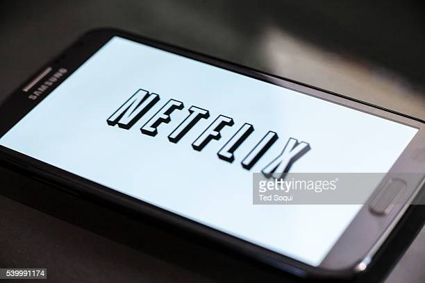 The new Netflix logo on a mobile phone Netflix streams media to over 50 million subscribers globally