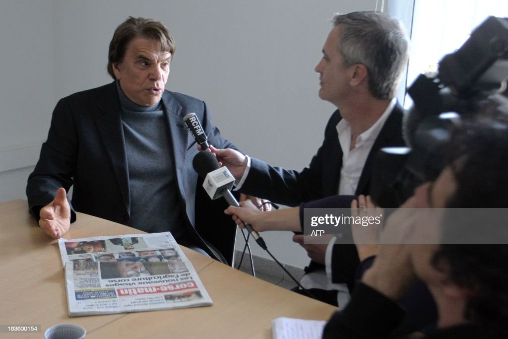The new owner of the Nice Matin press group Bernard Tapie (L) talks to journalists after meeting the group's employees on March 13, 2013 at the group's printing house in Bastia, Corsica. AFP PHOTO / PASCAL POCHARD-CASABIANCA